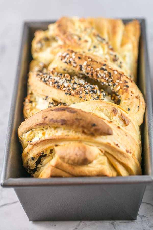 a loaf pan containing a freshly baked loaf of swirled everything bagel babka with a golden crust
