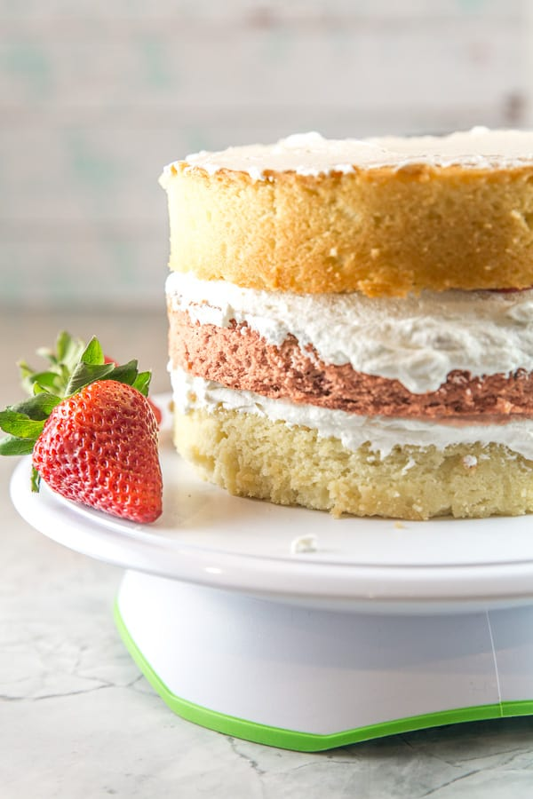 a three layer strawberry layer cake stacked but not yet frosted