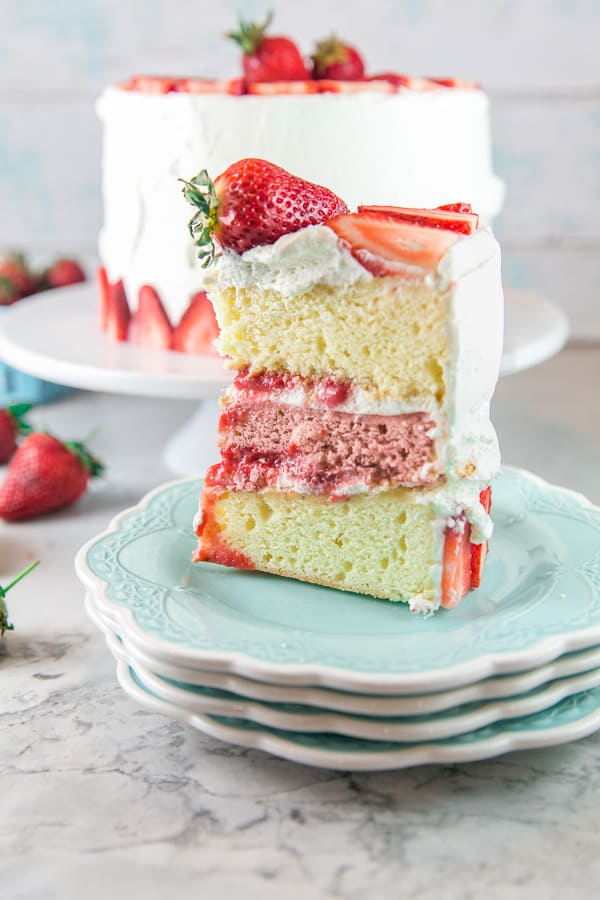 a cut slice of a three layer strawberry layer cake on blue dessert plates with vanilla and strawberry layers of cake