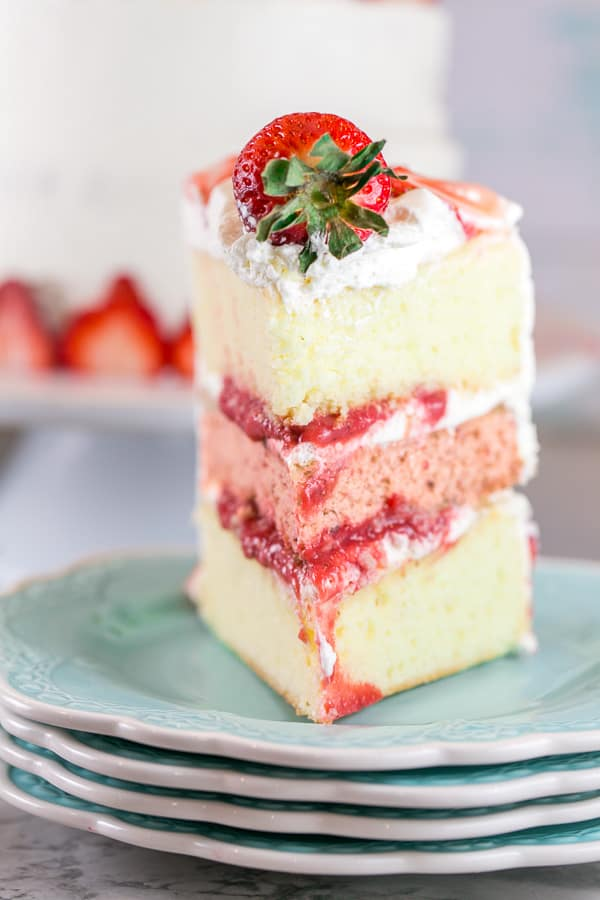 straight on view of a slice of strawberry layer cake showing the strawberry puree filling between each layer
