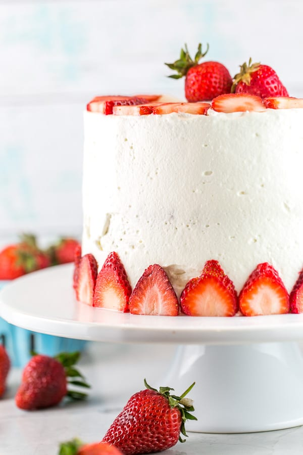 a three layer strawberry cake decorated with sliced strawberries on a white cake stand