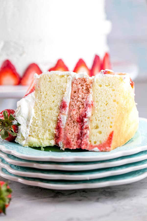 one slice of three layer strawberry layer cake on its side on a stack of blue dessert plates with the rest of the cake in the background