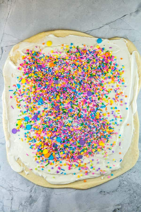 babka bread dough rolled out into a rectangle and covered with cream cheese filling and a layer of sprinkles