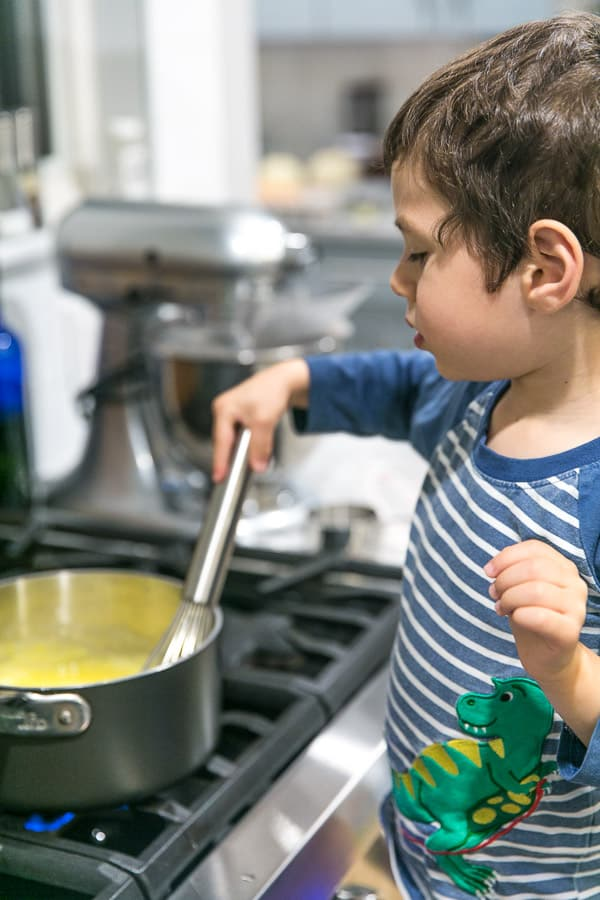 a 4 year old boy standing at the stove whisking a pot full of lemon curd