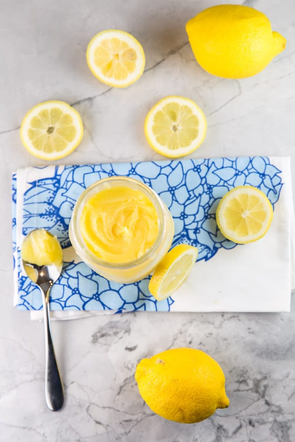 overhead view of a jar of lemon curd with a spoonful of the curd on a decorative blue dishtowel