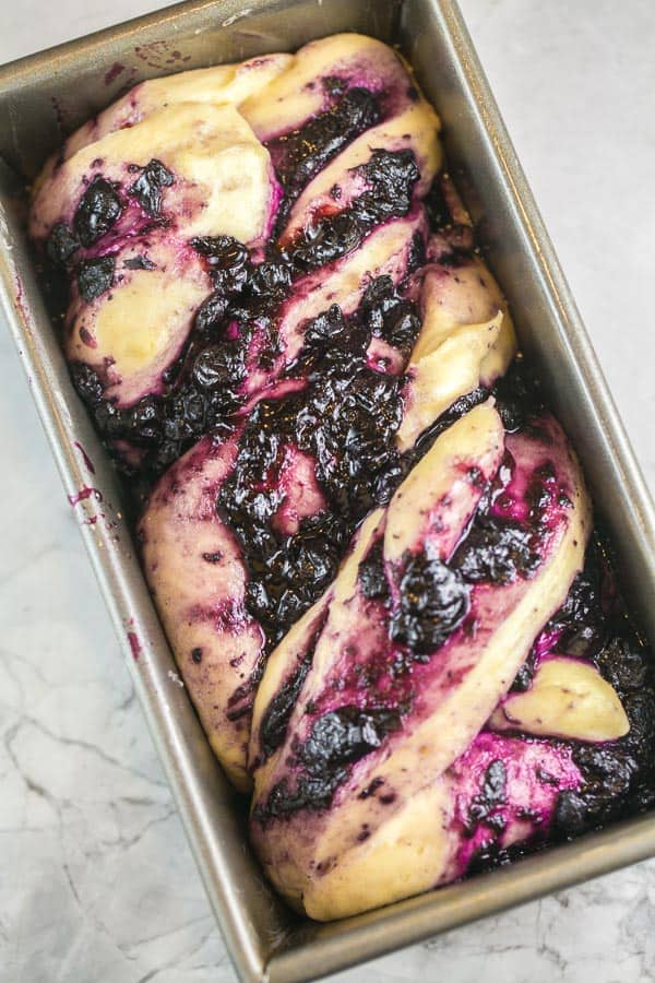 swirled blueberry babka dough in a loaf pan waiting to be baked
