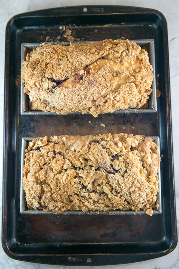overhead view of two loaves of baked blueberry babka covered in crunchy golden almond struseul