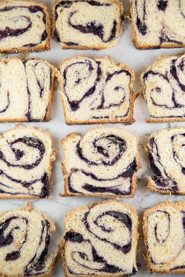 overhead view of 16 slices of blueberry babka showing the purple fruit swirl running through each slice