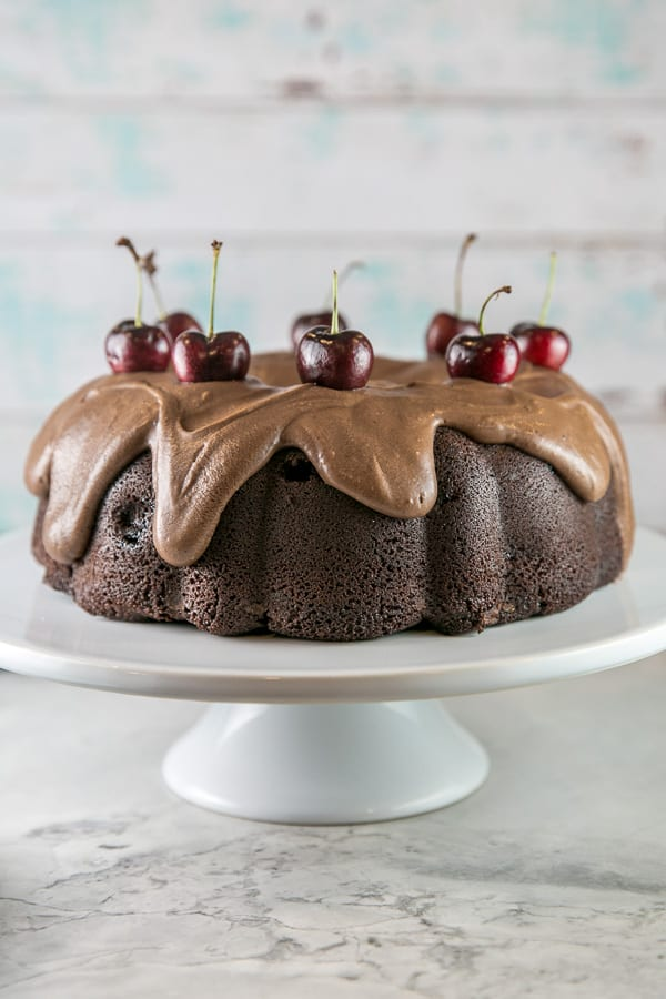 a chocolate cherry bundt cake covered in fudge frosting and topped with fresh cherries on a white cake stand