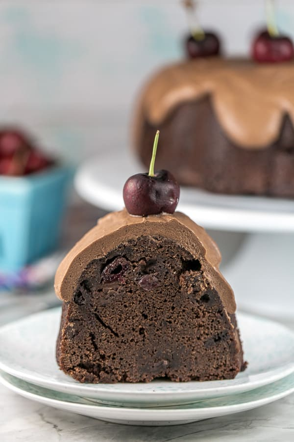 one slice of chocolate cherry bundt cake on stack of dessert plates showing the dark chocolate interior and thick layer of fudge frosting