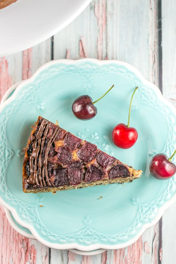 one slice of a chocolate chip cherry upside down cake on a bright blue dessert plate with three fresh cherries a decoration