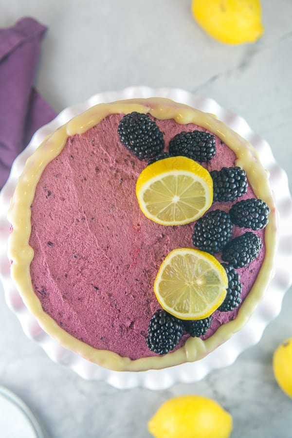 overhead view of a lemon curd layer cake decorated with blackberry frosting, lemon glaze, slices of lemon, and whole blackberries
