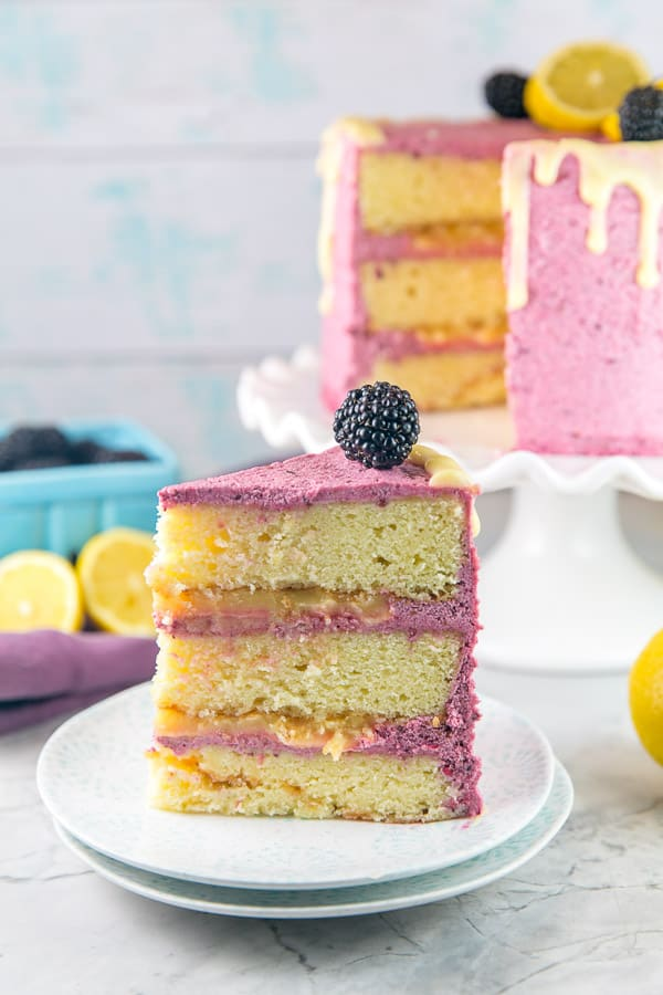 a slice of lemon curd cake showing three layers of cake, lemon curd filling, and blackberry buttercream frosting