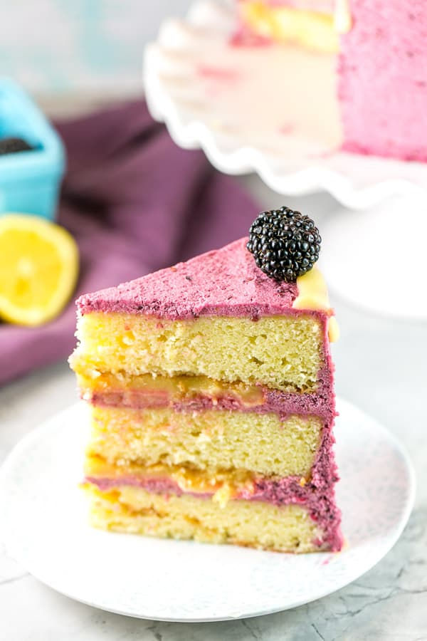 a slice of lemon curd cake with blackberry buttercream frosting on a white dessert plate