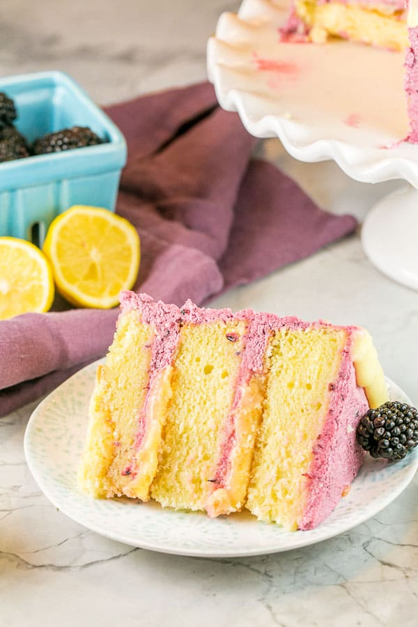 a slice of triple layer lemon curd cake with blackberry buttercream on its side with fresh lemons and blackberries visible in the background