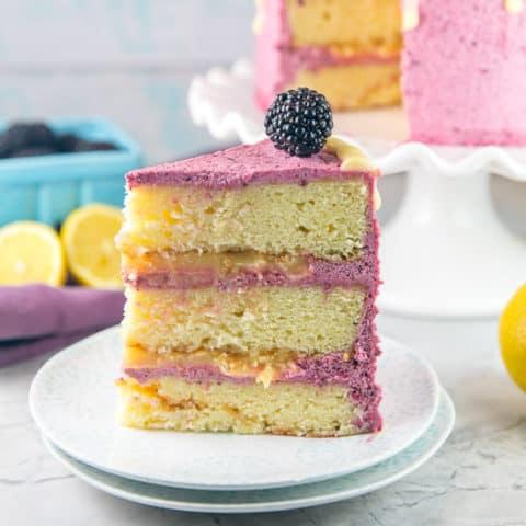 Lemon Curd Cake with Blackberry Buttercream Frosting: a triple level layer cake with lemon cake from scratch, filled with homemade lemon curd, and covered in fresh blackberry frosting and a lemon glaze. The perfect homemade birthday cake for lemon lovers! #bunsenburnerbakery #lemoncake #lemoncurd #layercake #birthdaycake
