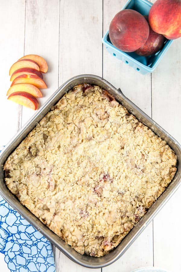 overhead view of a square baking dish filled with peach pie bars covered in oatmeal crumble next to sliced peaches