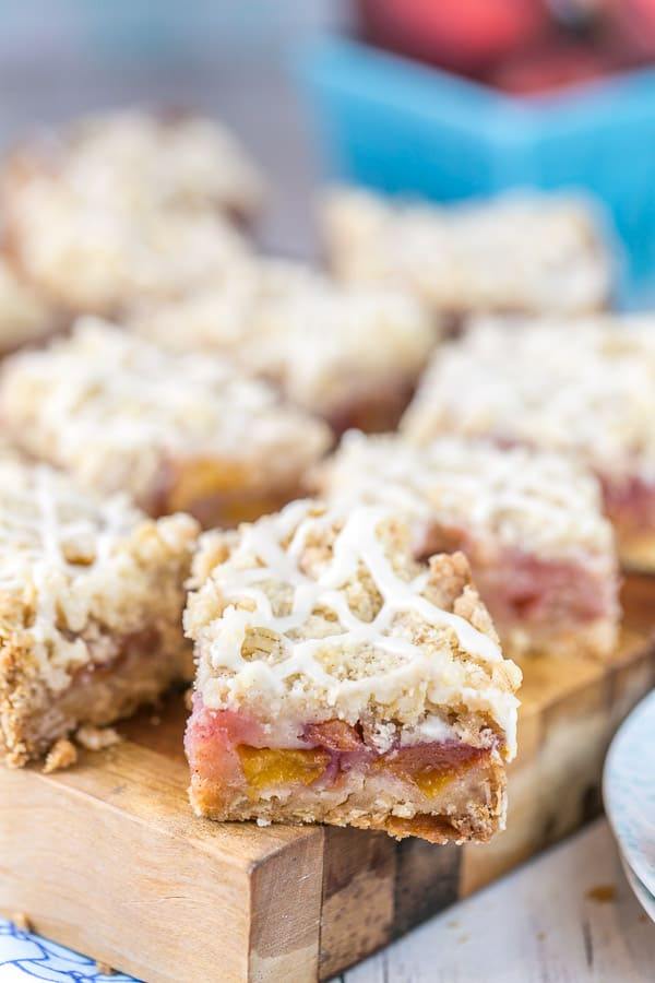 closeup view of the side of a peach pie bar showing the thick oatmeal shortbread crust and fresh peach filling
