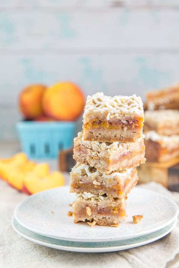four peach pie bars stacked on top of each other in front of a basket of peaches and a cutting board with more sliced pie bars