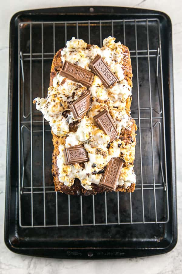 overhead view of a loaf of s'mores babka covered in toasted marshmallows, graham crackers, and squares of melted chocolate