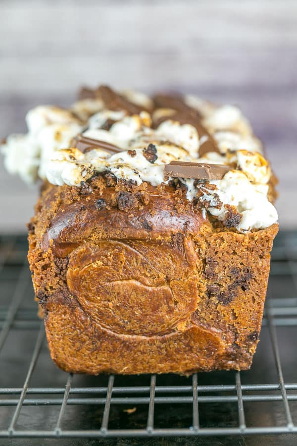 side view of a loaf of s'mores babka showing the outside swirls of the bread and the gooey marshmallow topping