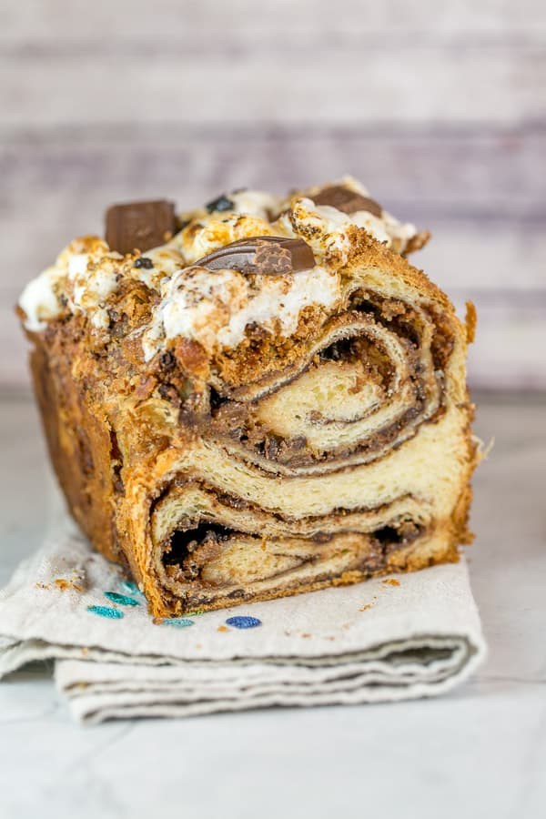 half a loaf of s'mores babka bread sliced to show the swirls of chocolate and marshmallow inside