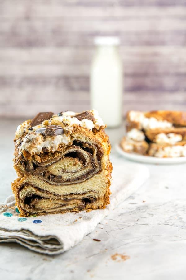 half a loaf of s'mores babka with slices of bread and a glass milk container in the background