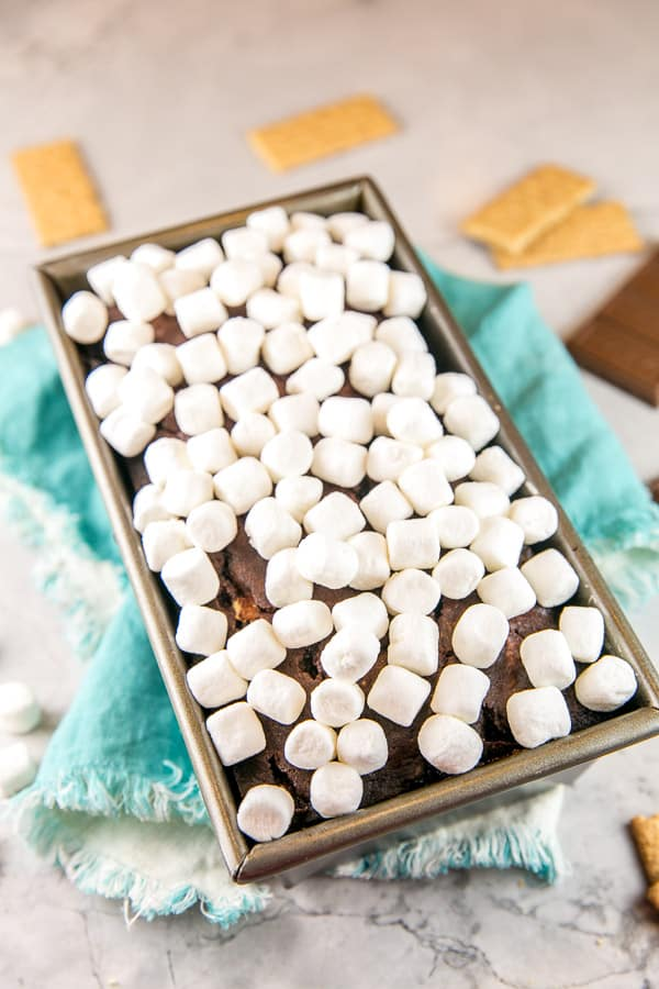 a chocolate graham cracker quick bread in a loaf pan covered with miniature marshmallows on a blue kitchen towel