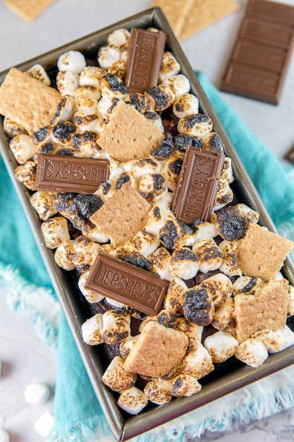 s'mores quick bread in a loaf pan covered with toasted marshmallows, graham crackers, and squares of chocolate