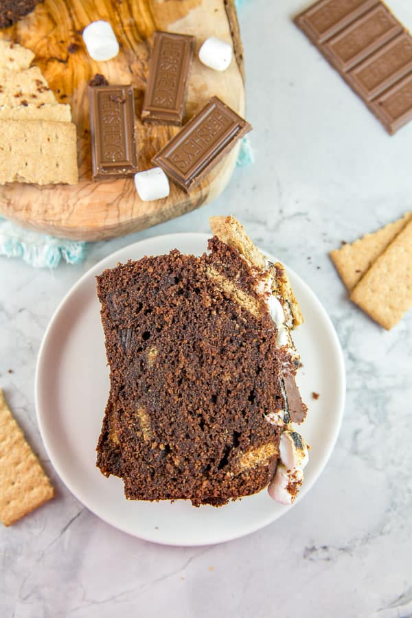 a slice of chocolate quick bread with visible pieces of graham crackers, topped with toasted marshmallow and squares of chocolate