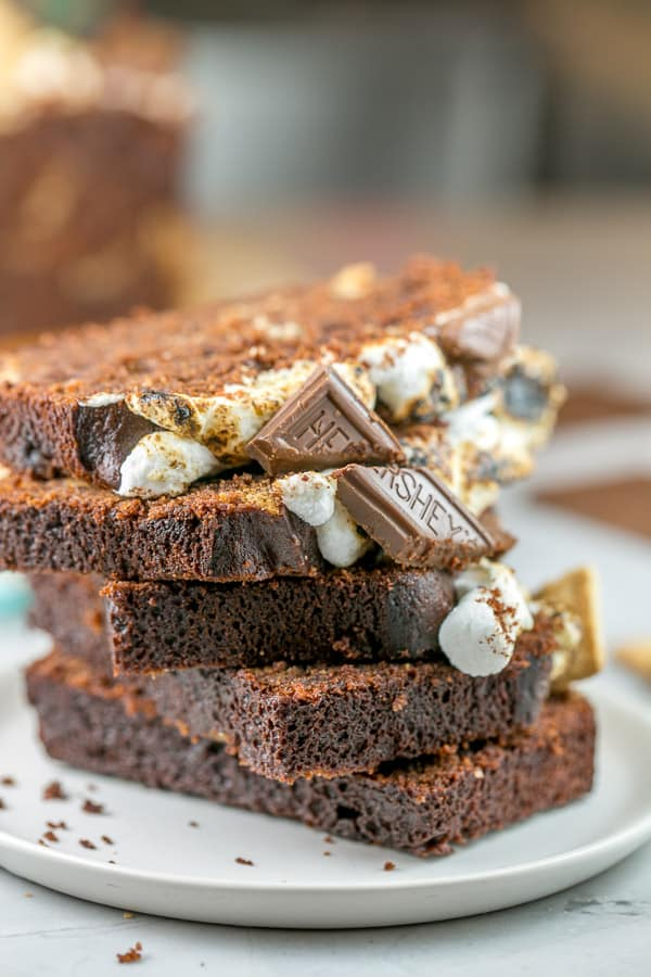slices of s'mores quick bread covered in toasted marshmallows and squares of chocolate stacked vertically on a plate