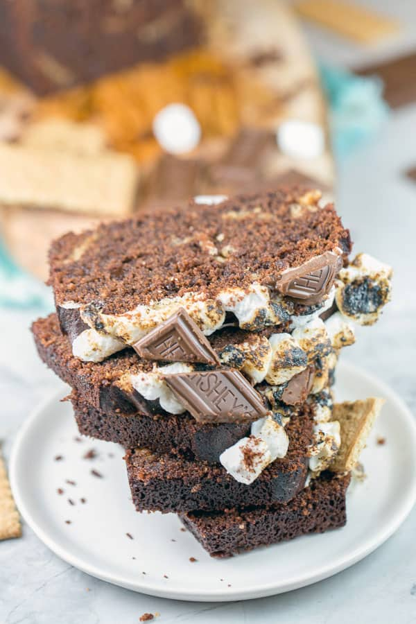 a tower of slices of chocolate s'mores quick bread stacked on a dessert plate