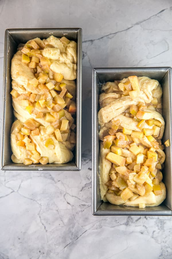 overhead photo of two loaf pans with honey apple babka dough twisted and filled with apples before baking