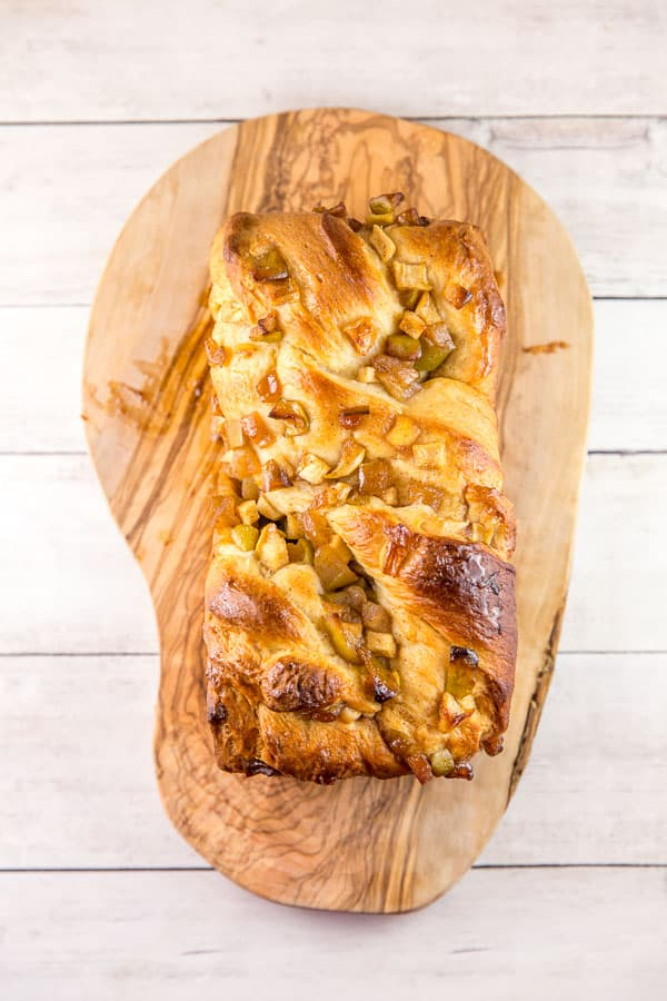a large loaf of honey apple babka on a wooden board