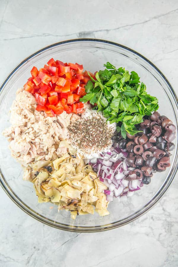 overhead view of a glass mixing bowl with piles of light chunk tuna, red bell pepper, artichoke hearts, red onion, greek olives, parsley, mayo, and italian herbs