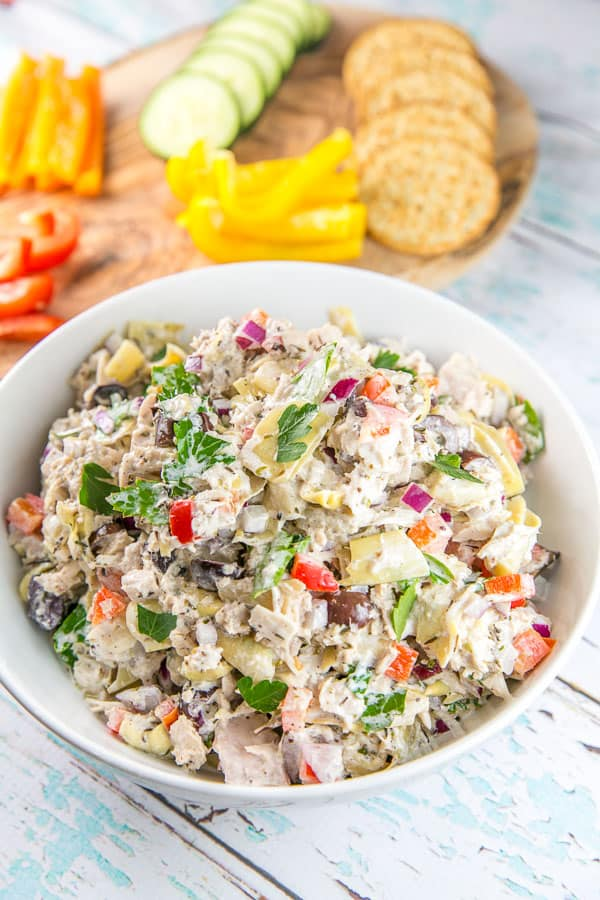 a large white bowl full of mediterranean tuna salad with cut vegetables and crackers in the background