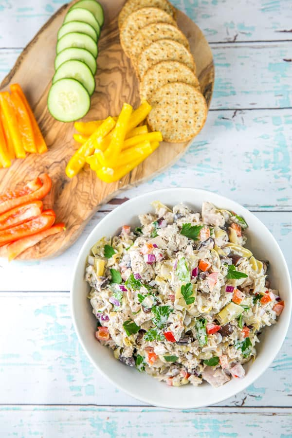 colorful mediterranean tuna salad surrounded by cut strips of red, yellow, and orange bell pepper, sliced cucumber, and round crackers