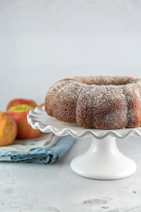 side view of an apple cider donut cake on a white serving plate with apples in the background