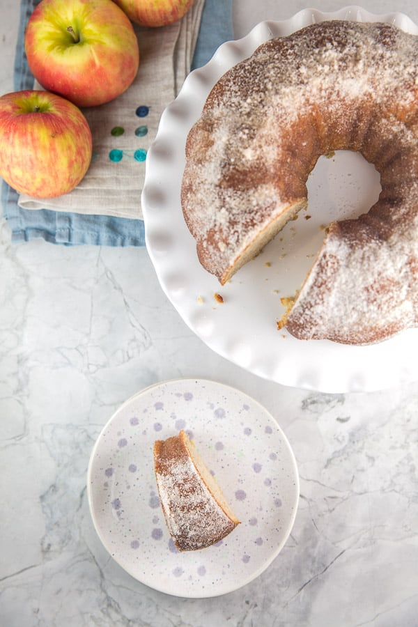 an apple cider donut flavored bundt cake with one slice removed and served on a purple polka dot dessert plate