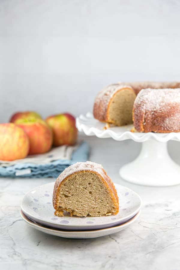 one slice of an apple cider donut bundt cake on a dessert plate with the rest of the cake and a pile of apples visible in the background