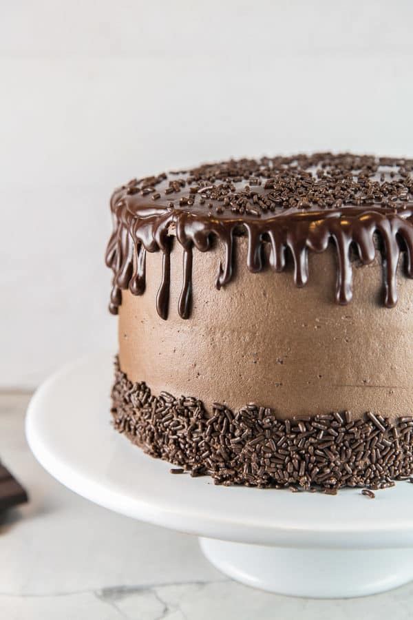 a three layer chocolate layer cake covered in chocolate buttercream frosting with chocolate ganache dripped down the side with chocolate sprinkles along the bottom of the cake and scattered across the top
