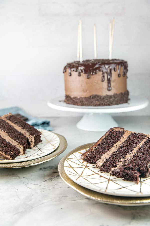 two slices of chocolate layer cake with thick layers of fluffy chocolate buttercream frosting on decorative gold dessert plates