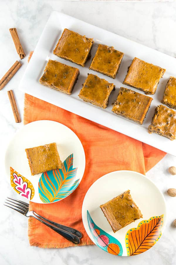 two chocolate chip pumpkin pie bars on decorate dessert plates with a tray of more pie bars on a white serving plate