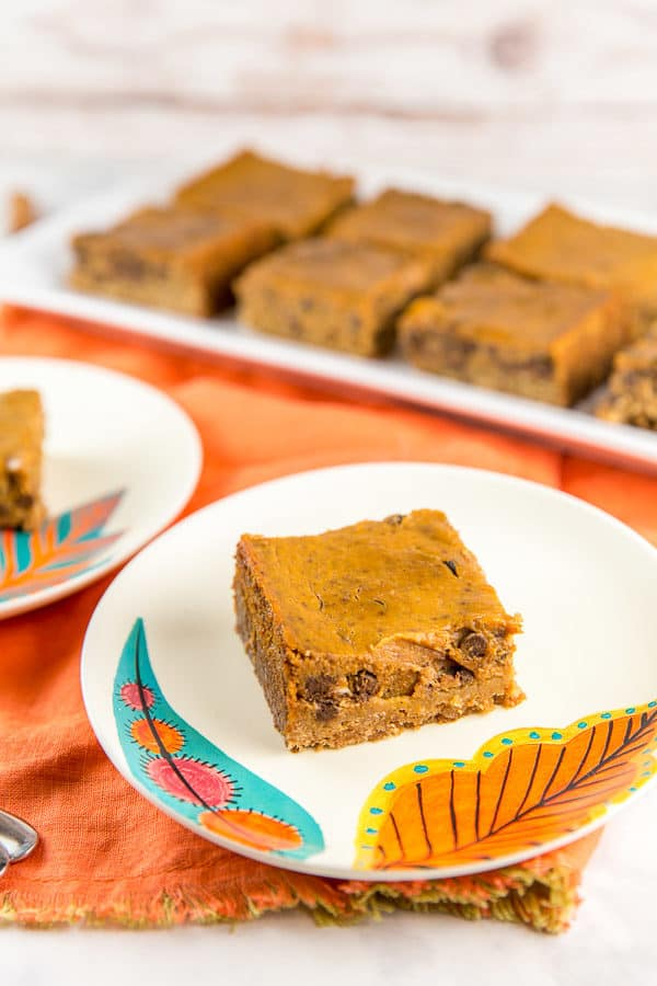 a chocolate chip pumpkin pie bar on a fall themed dessert plate on an orange cloth placemat with a tray of pumpkin pie bars in the background