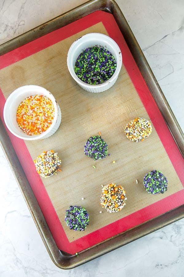 six balls of chocolate cooke dough rolled in sprinkles with two white bowls filled with two different colors of halloween themed sprinkle blends