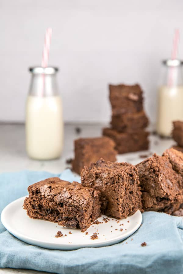 a pile of rich brown chewy brownies on a white dessert plate with two glass bottles of milk in the background