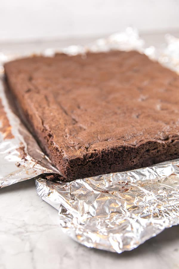 a sheet of brownies lifted out of the pan using foil handles