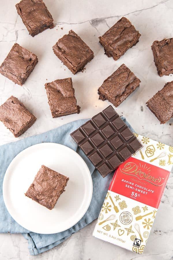 squares of brownies spread on a white marble counter with one brownie on a white dessert plate next to squares of baking chocolate and a Divine chocolate baking bar