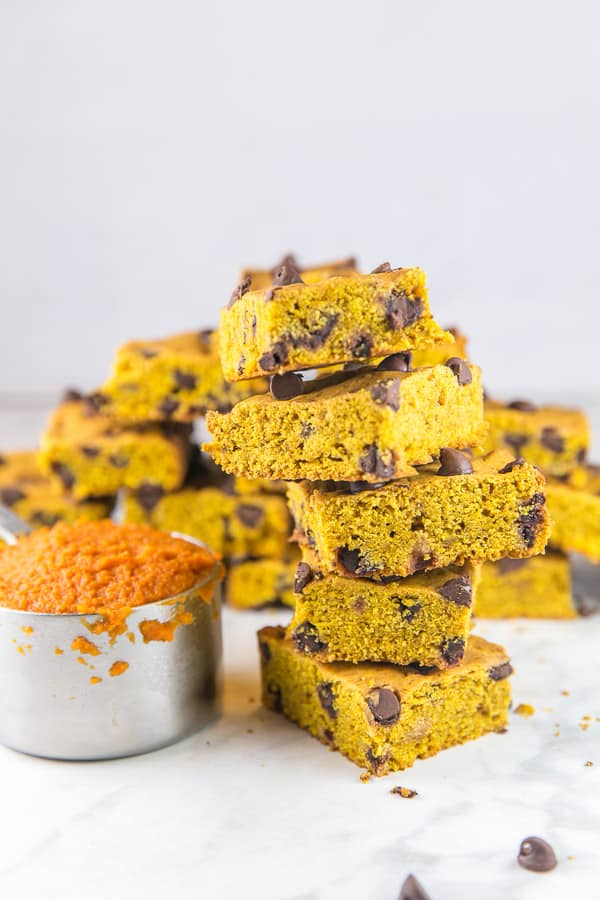 a stack of pumpkin chocolate chip cookie bars next to a measuring cup filled with pumpkin puree