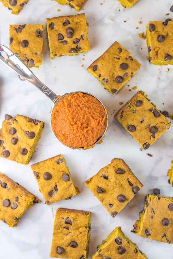overhead view of pumpkin chocolate chip cookie bars cut into squares and scattered on a marble countertop surrounding a measuring cup filled with pumpkin puree